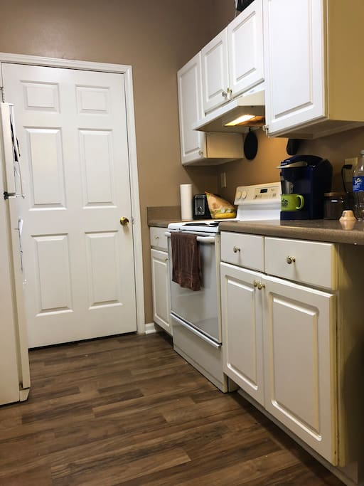 Full kitchen available stocked with pots, pans, plates, cups, and silverware . Laundry room through door.