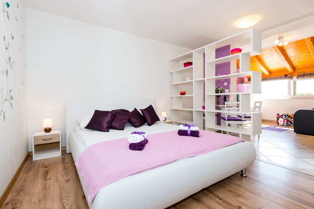 large double bed (sleeping area) and dinning area with living area with sofa and TV