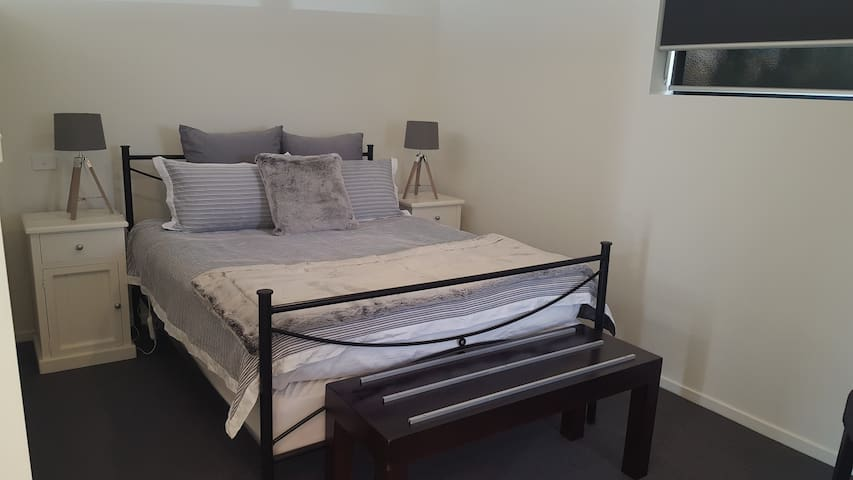 Studio bedroom- Queen  bed with privacy wall separating living area.