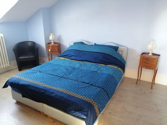 Chambre avec lit double, fauteuil et armoire de rangement