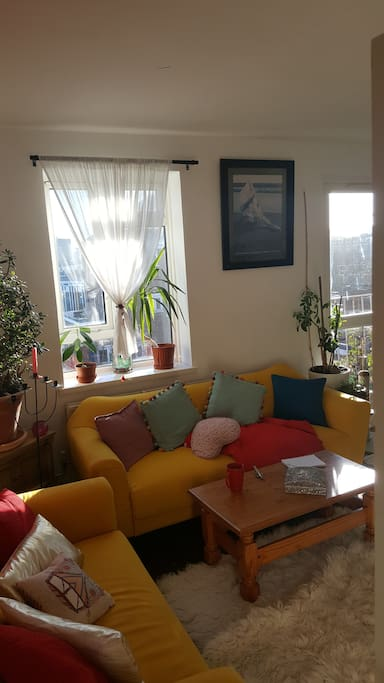 Shared living room with balcony door and window letting in lots of light