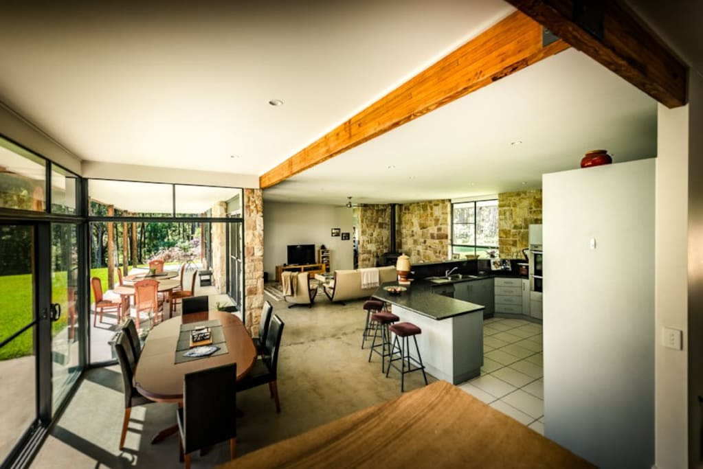 Huge open living dining and kitchen opens to outdoor veranda, lawns and forest.