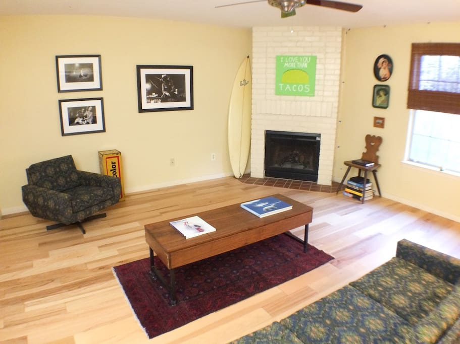 Spacious living room, with hickory floors, unique mid-century furniture, and original artwork.