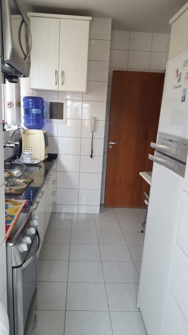 Cozinha completa, fogão, forno elétrico, microondas, geladeira e utensílios.