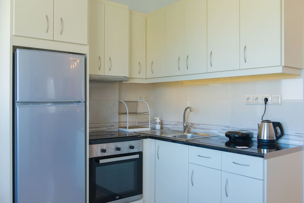 The fully equipped kitchen has kitchen utensils and crockery.