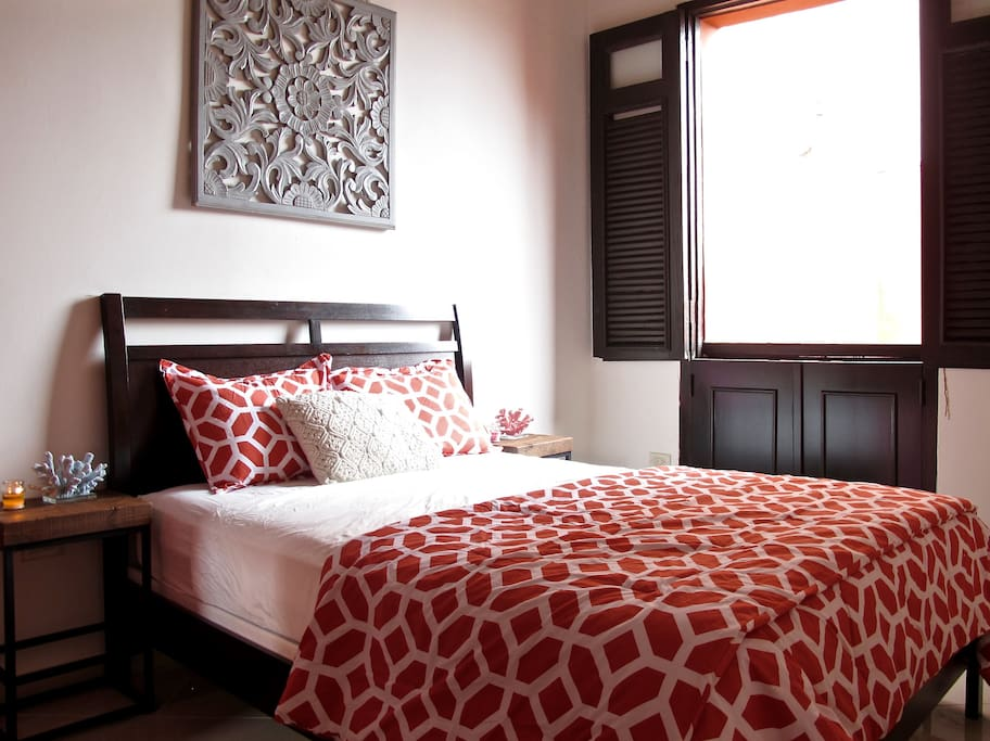 Master bedroom features a queen sized bed, nightstands and an armoire