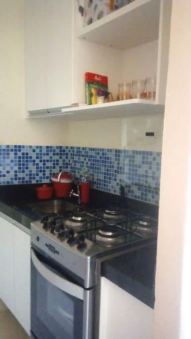 Cozinha com armários, forno, fogão, geladeira, mesa com 2 banquetas e utensílios domésticos.
