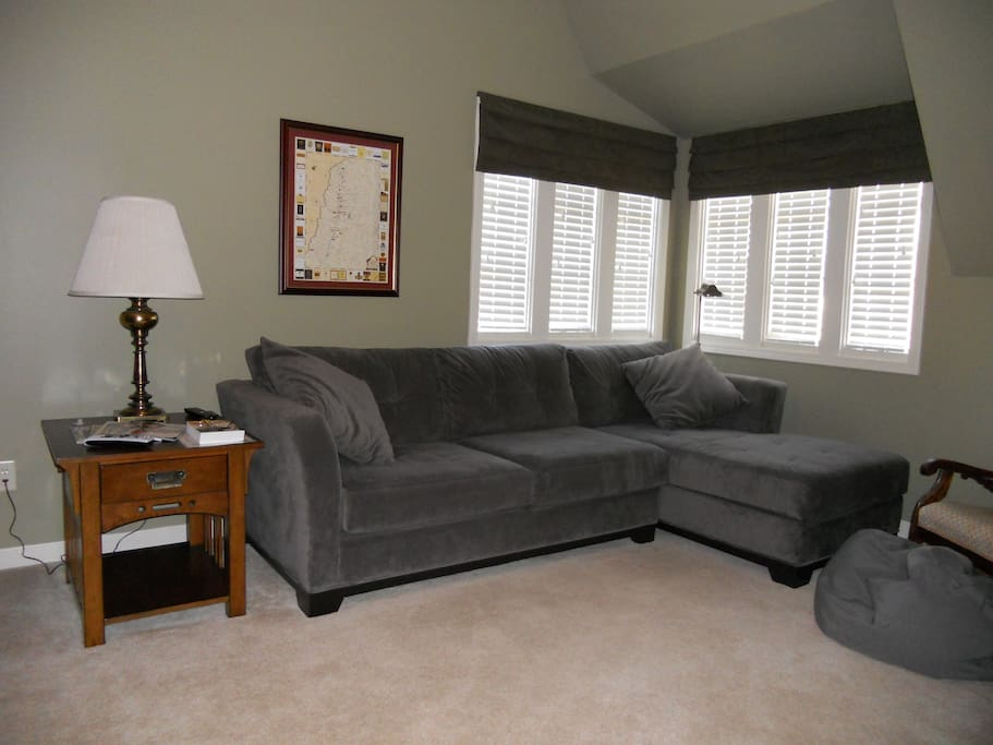 Comfortable, private sitting area with couch and 55-inch HDTV.  Includes work space with desk, office chair and Wifi.