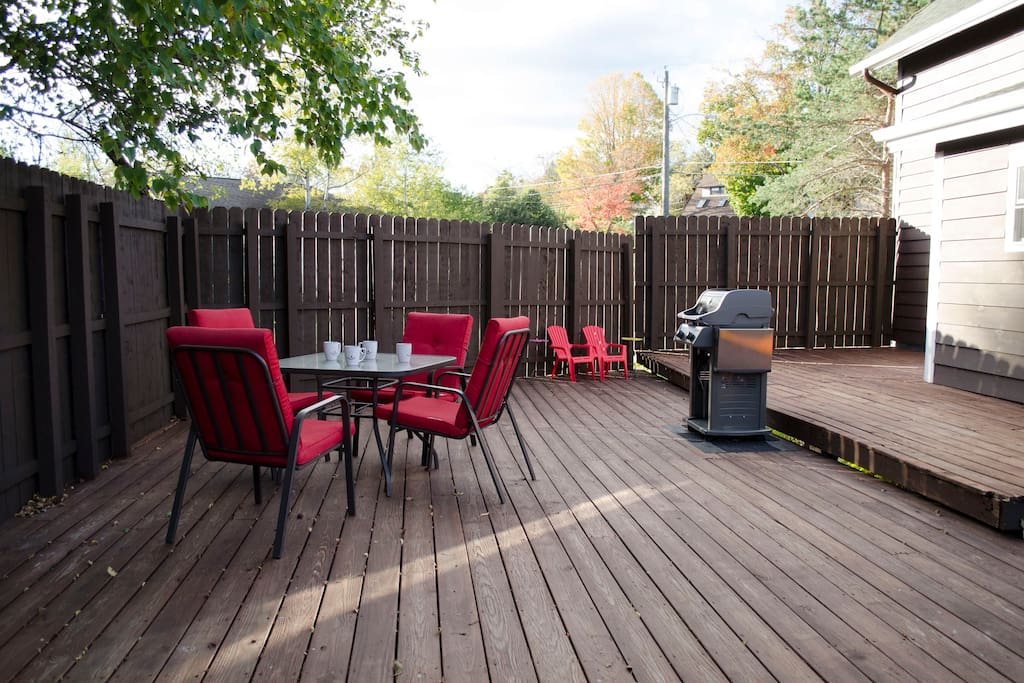 Large fenced in deck with dining set and Weber grill