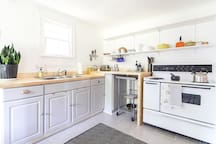 Alternate view of open, bright kitchen, with vintage stove, butcher-block countertops, and restaurant-grade stainless steel rolling cart for more surface area as needed.