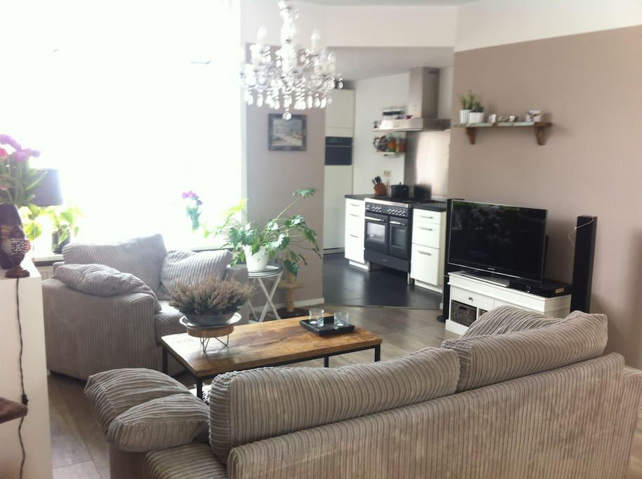 Ruime knusse woonkamer, veel licht. Hoog plafond. 3-persoonsbank en 1,5 zitstoel. Digitale televisie. CD/DVD speler.