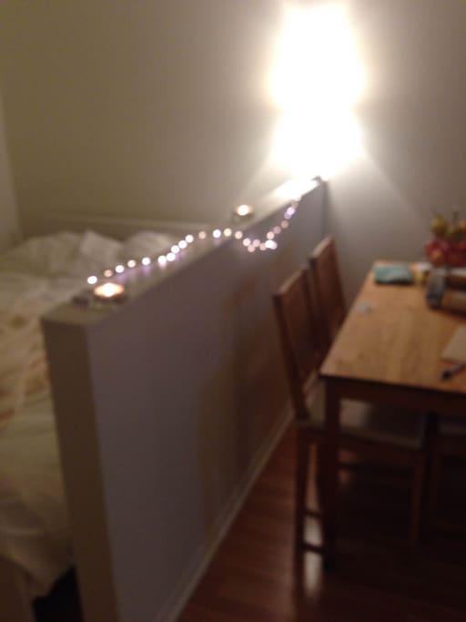 vue coin chambre lit double, séparation muret, et table en bois 4 chaises
