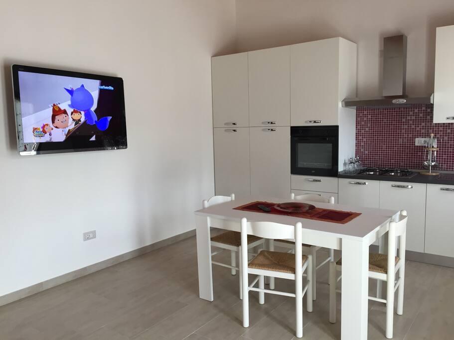 sala-cucina con tavolo e sedie - tv