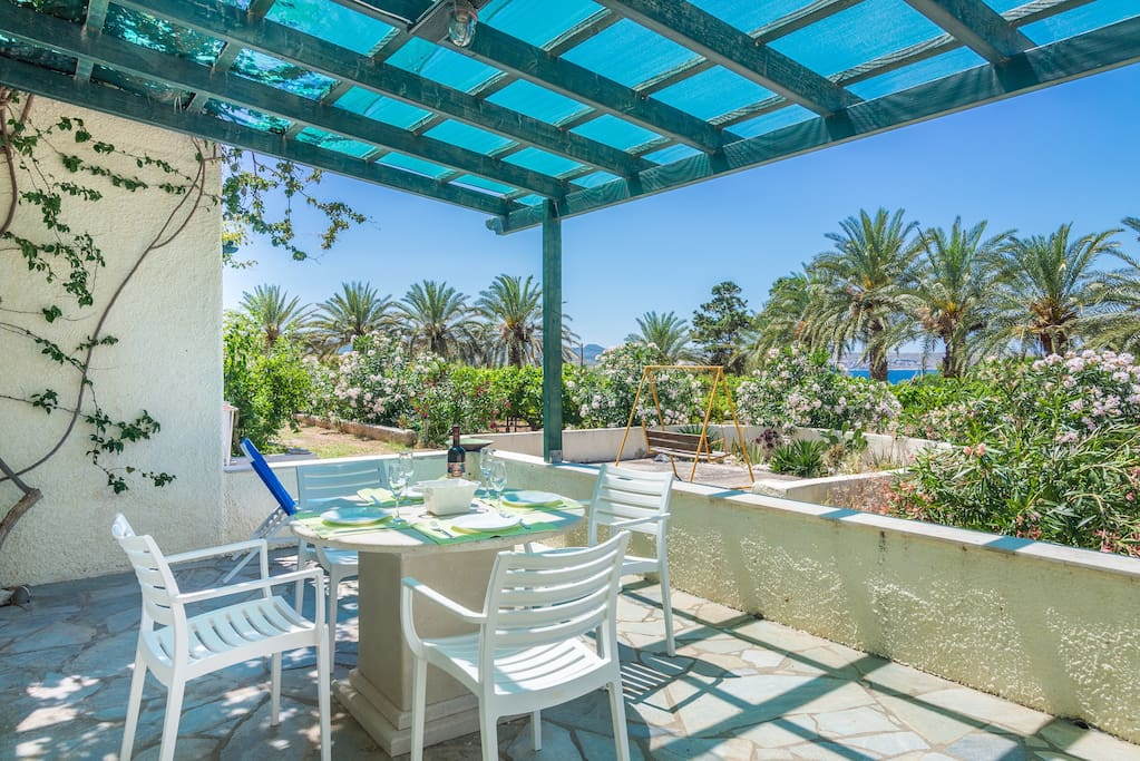 The northwest patio has ample space for your meals. In front of the patio lies the property's vine yeard and old palm trees. There is a Weber coal BBQ for your cooking needs