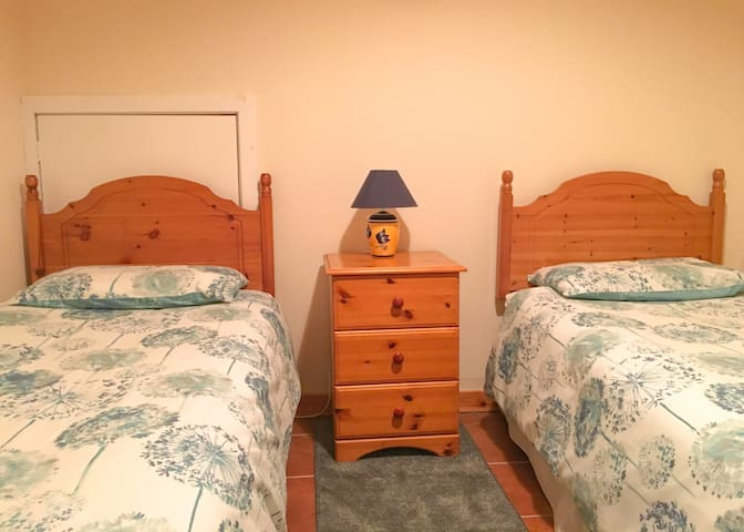 The second bedroom with two single beds, bedside cabinet and wardrobe
