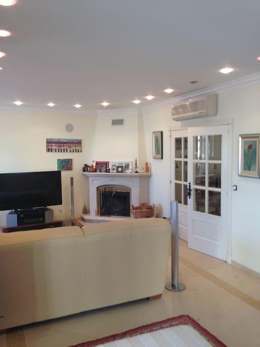 Sala de estar com acesso a sala de leitura envidraçada e terraço