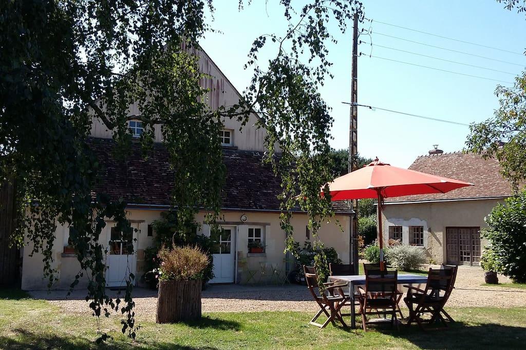 La maison ,côté entrée et cuisine, avec son jardin  arboré.