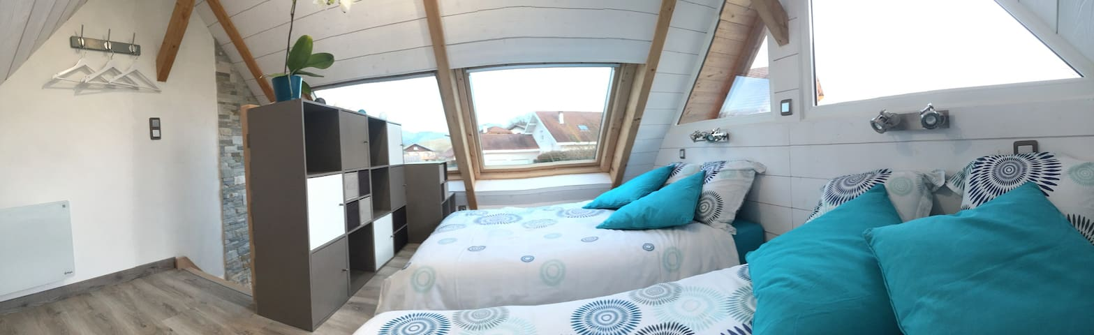Chambre avec 2 lits doubles, matelas posés au sol, la hauteur sous plafond ne permettant pas la présence de sommiers.