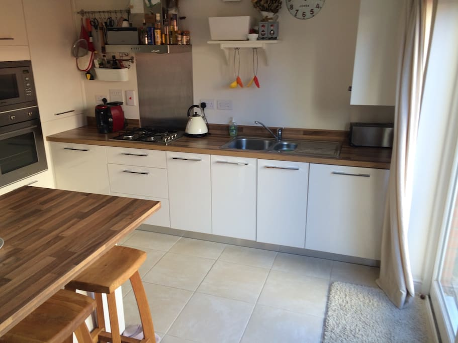 Fully equipped kitchen with breakfast bar and patio doors opening to garden