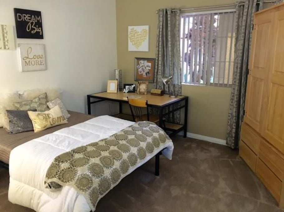bed room with commendable furnitures including a book table, a mini desk, a chest, and a full-size bed