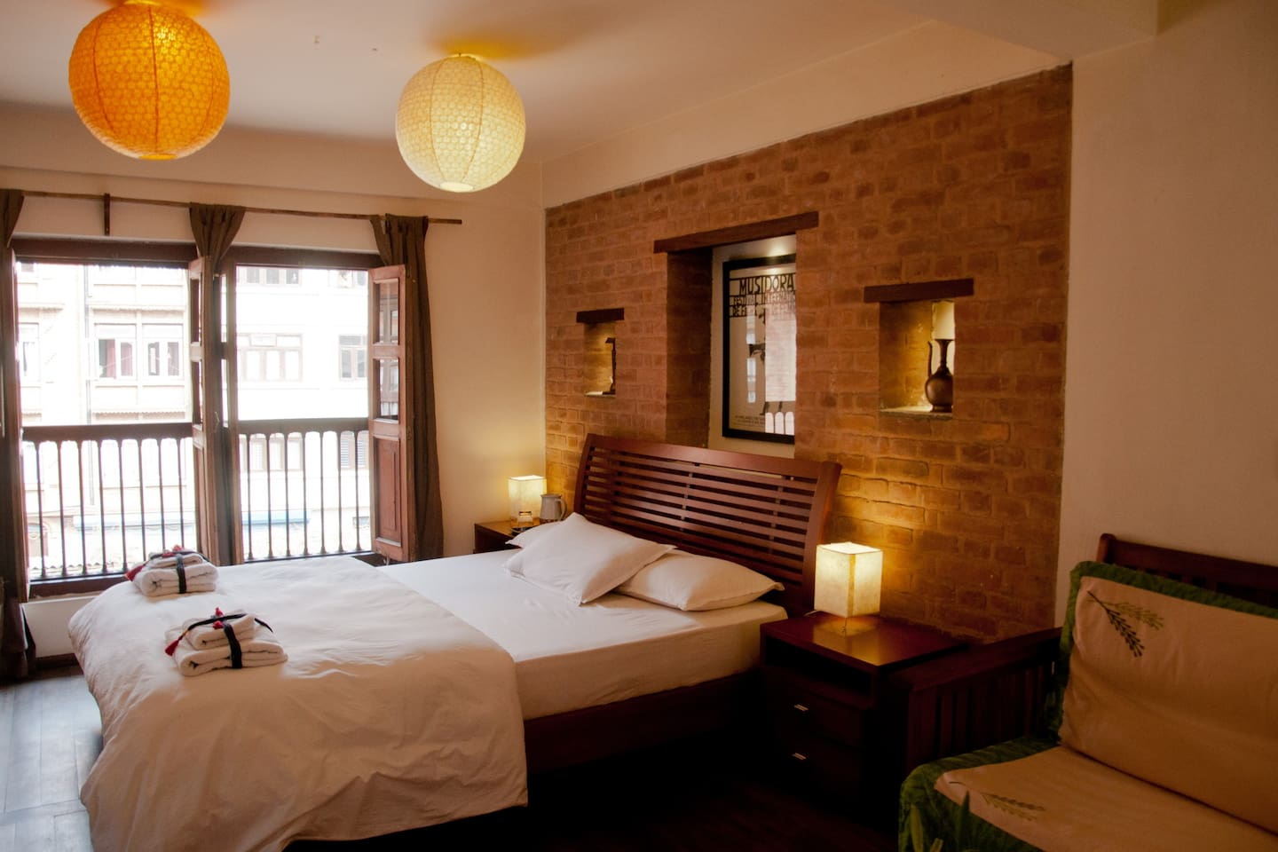 Spacious bedroom with king-bed and  view over a courtyard.