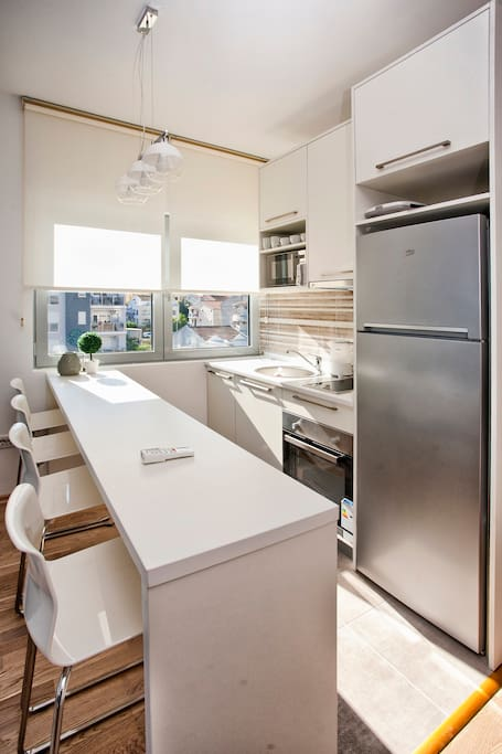 Kitchen with 4 people bar and appliances including dishwasher