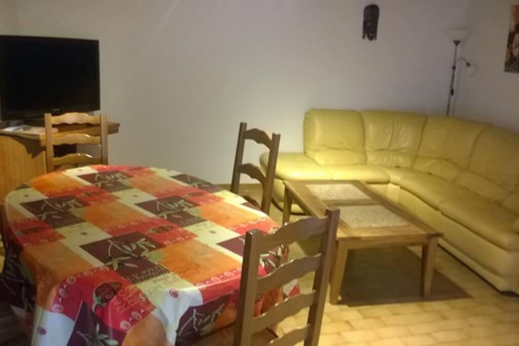 Un salon confortable spacieux avec écran plat ...