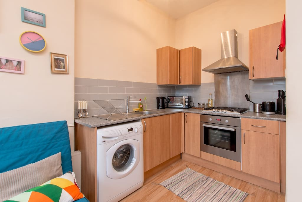 Kitchen with washing machine, microwave, toaster and kettle