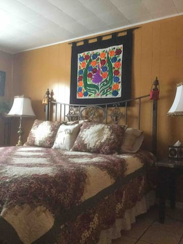 The king sized bed is dressed in beautiful linens and pillows.  The walls are lined with art and photos from our world travels.