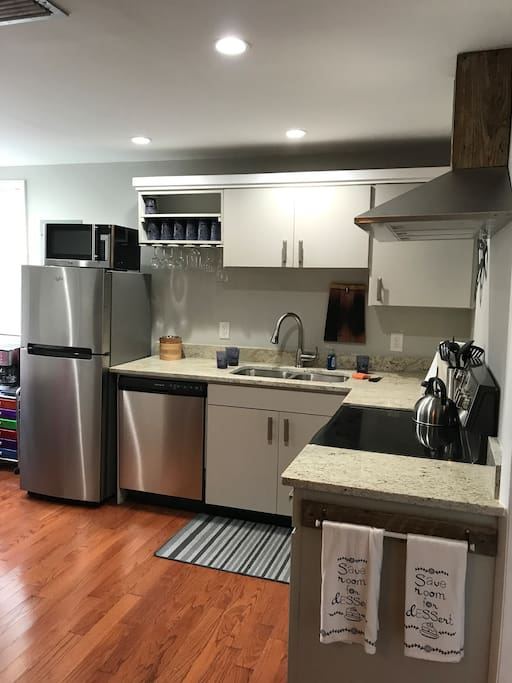 Fully stocked brand new kitchen with granite counter tops and stainless steel appliances