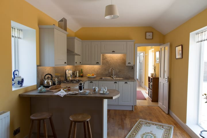 Fully equipped kitchen and sitting room with electric oven and gas hob, dish washer, breakfast bar