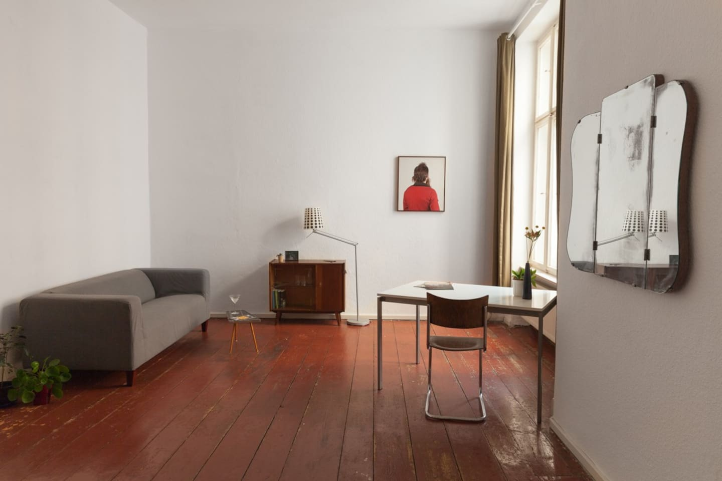 The 28m2 room is a so called 'Berliner Zimmer' (a spacious room that connects the front building apartment to the side wing) and has the original wooden floor in oxblood red
