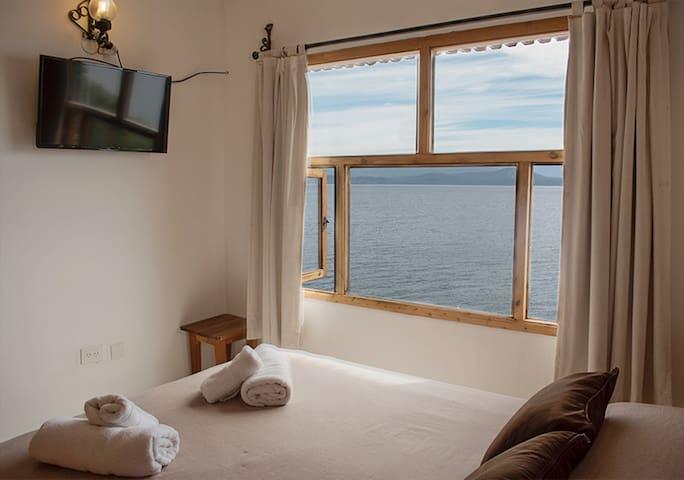 Habitación con cama matrimonial , TV , y vista al lago.