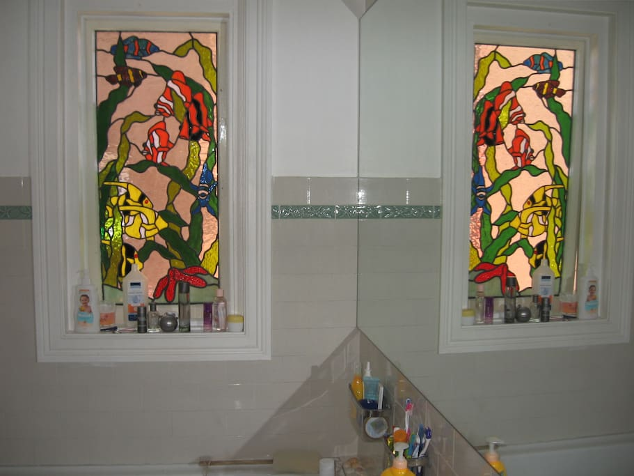 Bathroom features wall-length mirror and stained glass window