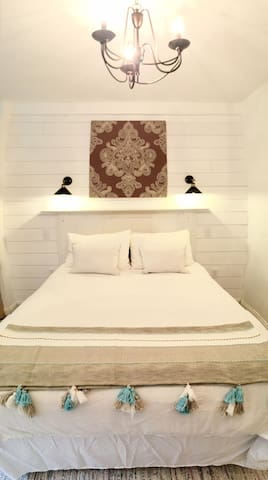 A shiplap feature wall with antique fireplace mantle headboard and elegant side lighting will make you want to snuggle up in our pillow-top queen sized bed.