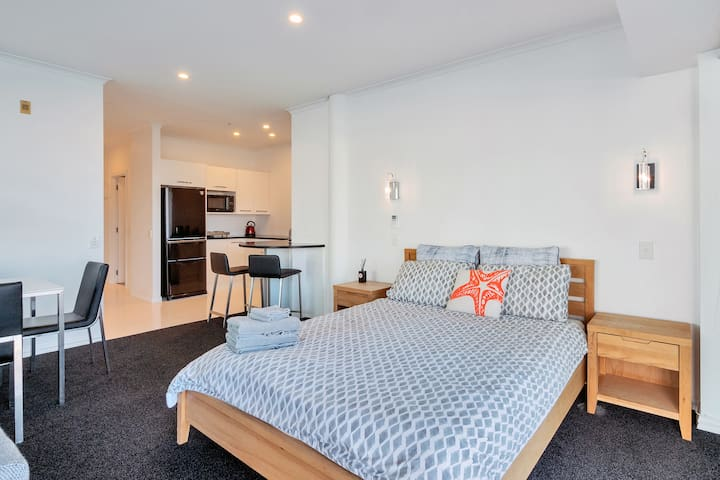 View of the queen-sized bed and fully equipped kitchen.  The bed linen is hotel quality, soft and breathable. It keeps you warm in the winter and cool in the summer.