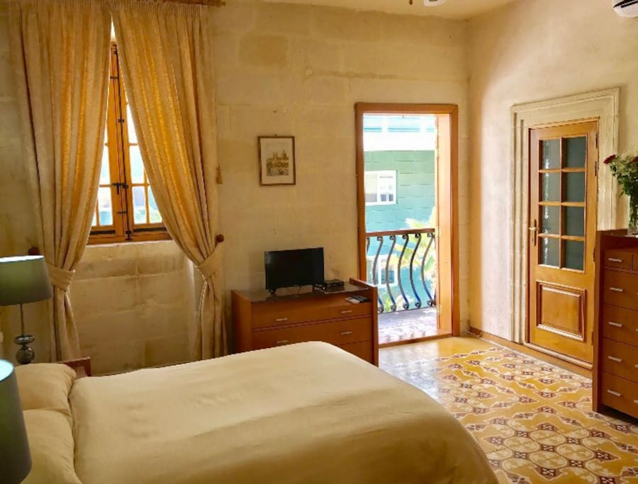 Large double bedroom with en-suite shower room and traditional Maltese floor tiles