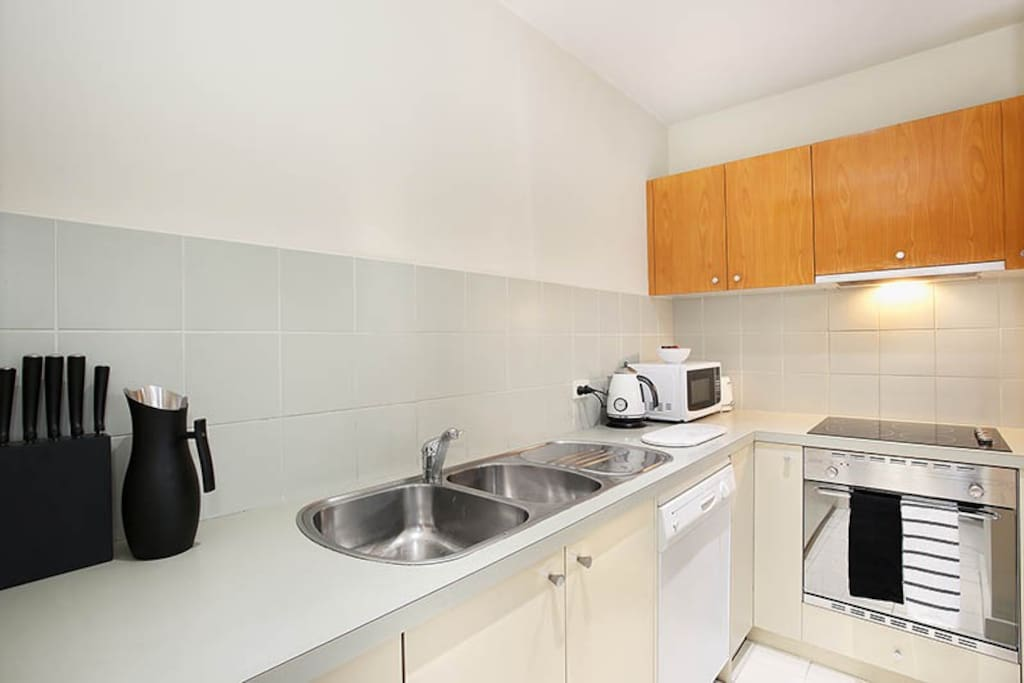 Dining area & kitchen in this 1-bedroom StayCentral St Kilda Serviced Apartment