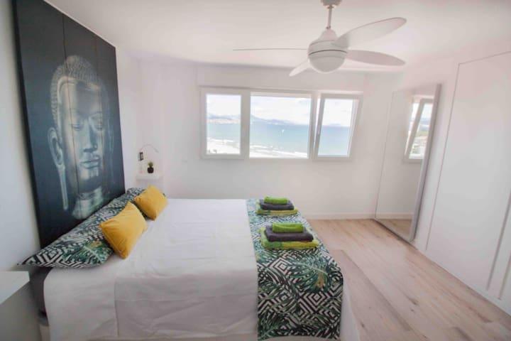Segunda habitación doble con vistas a toda la costa y al mar, cama de 150 por 190 cm, armario empotrado doble, ventilador programable y persiana automática y programable.