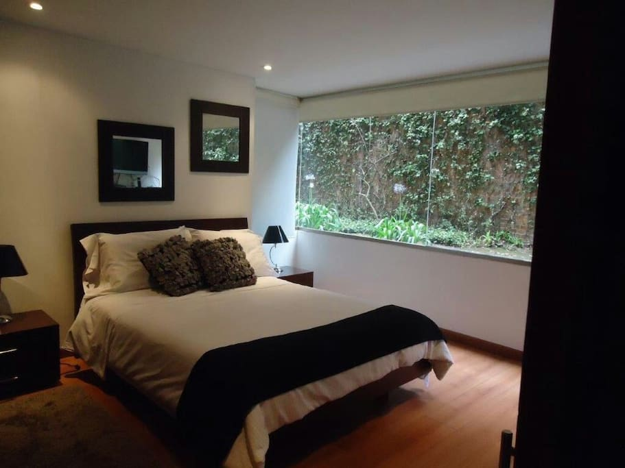 Comfortable queen size bed with  view of the garden. Perfect for resting in silence.