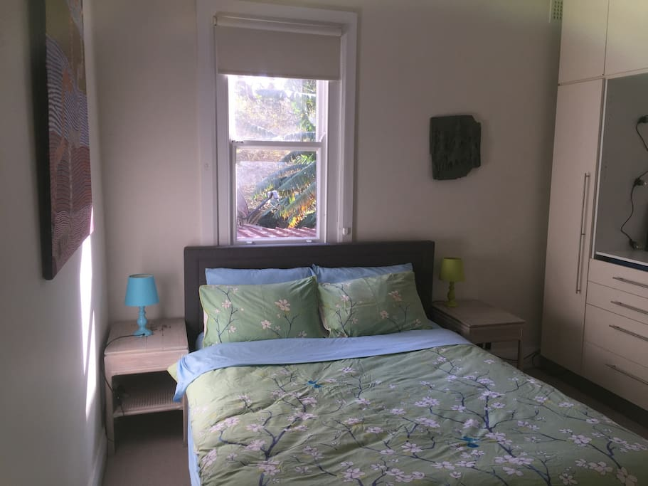 The second bedroom has a new queen size bed with bright afternoon sun overlooking the garden.