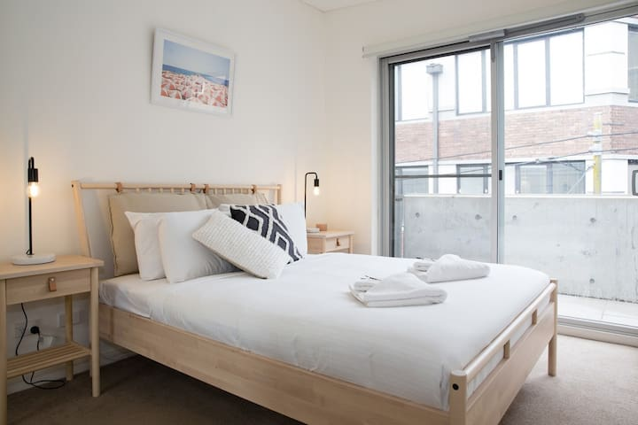 The queen bedroom features hotel-style premium linens and full-length windows allowing for natural light to stream in.
