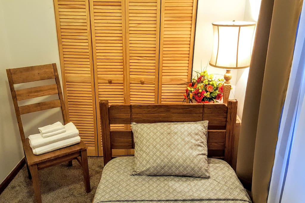 Single-sized bed with fresh linens and towels