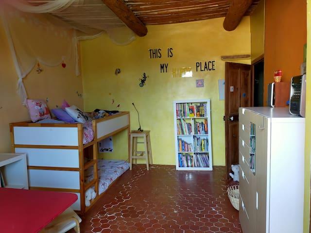 La chambre happy : lits superposés, deux lits une place. une armoire de rangement, un bureau et des étagères