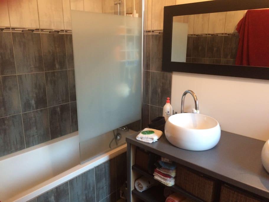 Salle de bain entièrement refaite à neuf possédant une baignoire, un double vasque, machine à laver et sèche linge à disposition. Un sèche cheveux reste à votre disposition si nécessaire.