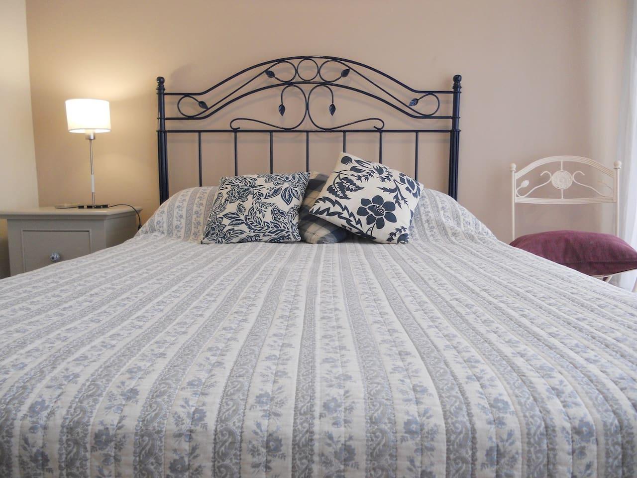 Dormitorio con una cama doble, aire acondicionado y salida a un pequeño balcón con vista a la peatonal Florida