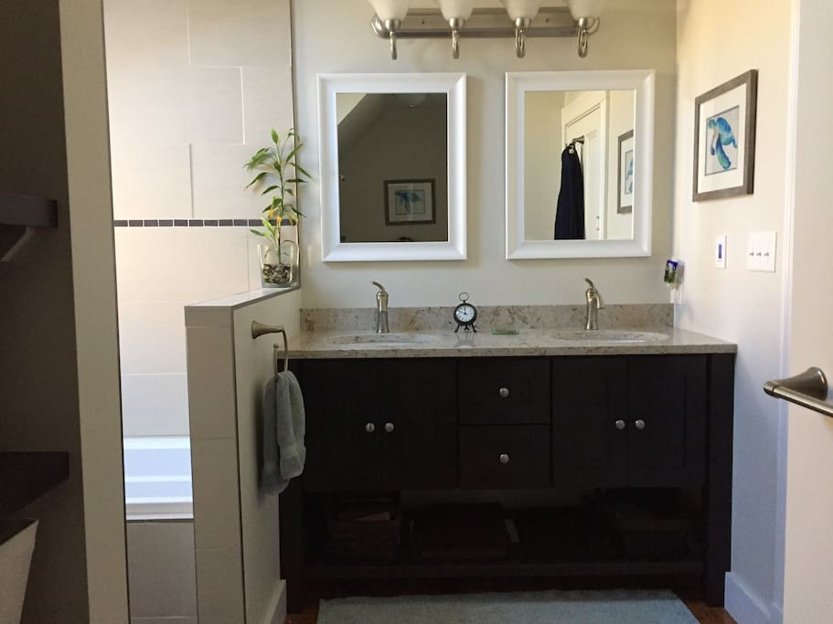 Double sinks, quartz countertops, and tons of natural light in this spacious bathroom
