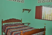 2 Bedrooms to accommodate 4 guests. Front bedroom with double bed, screened window with metal bar protection, shelves, fan, place to hang clothes.
