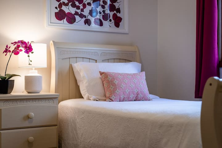 The Bouganvillea Room is a cozy space with a view of the garden and forest.