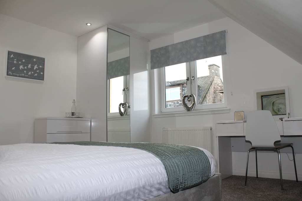 Bedroom with ample storage , dressing table and hairdryer.